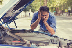 Stressed man with broken car looking at failed engine Royalty Free Stock Images