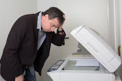 Stressed man in front of a copy machine Royalty Free Stock Photo