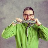 Stressed man in green shirt and glasses biting in his necktie royalty free stock images