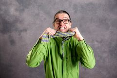 Stressed man in green shirt and glasses showing his teeth and ne royalty free stock image