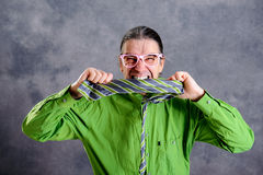 Stressed man in green shirt pink glasses biting in his necktie royalty free stock photography