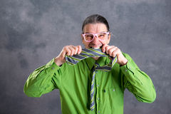 Stressed man in green shirt pink glasses biting in his necktie royalty free stock photos