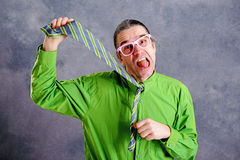 Stressed man in green shirt pink glasses strangle with necktie royalty free stock photos