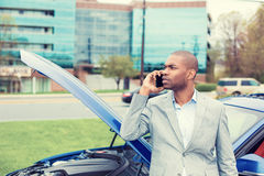 Stressed man having trouble with broken car opening hood calling for help on cell phone Stock Photography