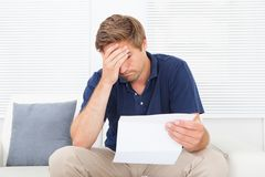 Stressed man holding bill at home Royalty Free Stock Image