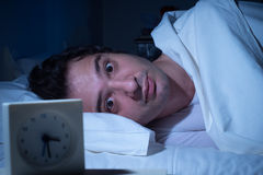 Stressed man insomnia. Stressed man suffering for insomnia can't sleep in his bed Stock Photography