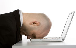 Stressed man and laptop. A stressed bald businessman with his forehead resting on the laptop computer keyboard Stock Photo