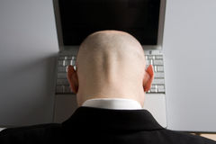 Stressed man and laptop. A stressed bald businessman with his forehead resting on the laptop computer keyboard Stock Image