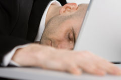 Stressed man and laptop. A stressed bald businessman with his forehead resting on the laptop computer keyboard Stock Photography