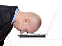 Stressed man and laptop. A stressed bald businessman with his forehead resting on the laptop computer keyboard Royalty Free Stock Images