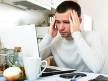 Stressed man with laptop. Portrait sadness man with laptop at table in home interior Stock Photos