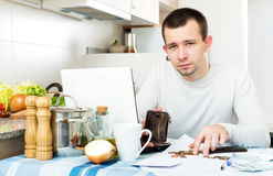 Stressed man with laptop. At table in home interior Stock Image