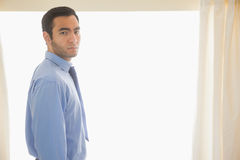 Stressed man looking at camera standing in front of a window Stock Image