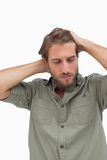 Stressed man looking down with hands on head Royalty Free Stock Photos