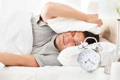 Stressed man looking at his alarm clock ringing Royalty Free Stock Image