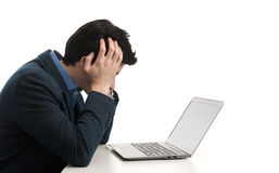 Stressed man looking at his laptop computer. With his head in his hands Stock Image