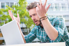 Stressed man looking at laptop with hands raised. Portrait of a stressed man looking at laptop with hands raised Royalty Free Stock Images