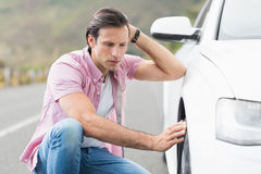 Stressed man looking at wheel Stock Photos