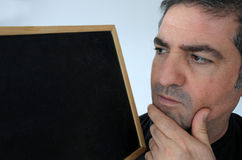 Stressed man looks at empty blackboard Royalty Free Stock Images