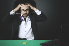 Stressed man loses in online poker. Stressed man with curly hair, loses in online poker gambling with chip and laptop on the table Stock Images