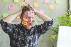 Stressed man with message on sticky notes over his face in offic Royalty Free Stock Photography