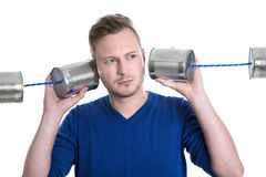 Stressed man overworked holding tin can phones isolated on white Royalty Free Stock Photo