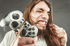 Stressed man playing on pad. Addiction. Stressed depressed young man playing gaming on pad. Angry guy with controller pad play console. Face expression Stock Image