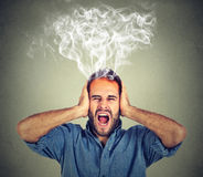 Stressed man screaming frustrated overwhelmed steam coming out up of head Royalty Free Stock Photo