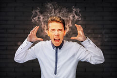 Stressed man screaming with smoke coming out of his ears Stock Photo