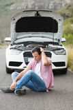 Stressed man sitting after a car breakdown Stock Image