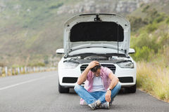 Stressed man sitting after a car breakdown at the side of the road Royalty Free Stock Images