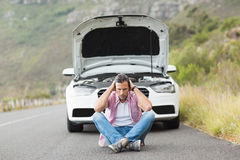 Stressed man sitting after a car breakdown Royalty Free Stock Image