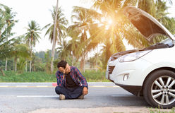 Stressed man sitting after a car breakdown. At the side of the road Royalty Free Stock Photo