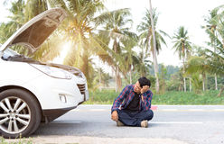Stressed man sitting after a car breakdown. At the side of the road Royalty Free Stock Photos