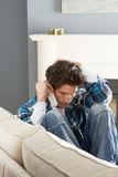 Stressed Man Sitting On Sofa At Home On Phone Royalty Free Stock Images