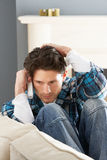 Stressed Man Sitting On Sofa At Home On Phone royalty free stock photography
