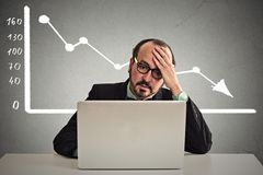 Stressed man sitting at table with financial chart going down stock image