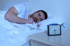 Stressed man trying to sleep in his bed. At night Stock Photos