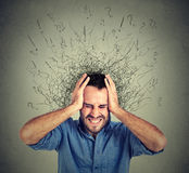 Stressed man upset frustrated has too many thoughts with brain melting into lines. Question marks. Obsessive compulsive, adhd, anxiety disorder. Negative human Royalty Free Stock Photo