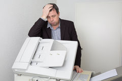 Stressed  man using a copy machine Stock Images
