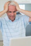 Stressed man using his laptop. At home in the kitchen Stock Image