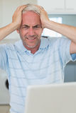 Stressed man using his laptop looking at camera. At home in the kitchen Royalty Free Stock Images