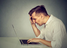 Stressed man working on laptop sitting at table. Side profile stressed man working on laptop sitting at table Royalty Free Stock Image