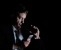 Stressed mature man drinking a beer while checking his cell phone while in the darkness stock image