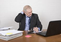 Stressed mature man at work looking at paperwork. Sitting at a desk Royalty Free Stock Images