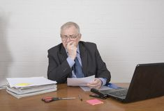 Stressed mature man at work looking at paperwork. Sitting at a desk Royalty Free Stock Photos