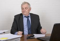 Stressed mature man at work looking at paperwork. Sitting at a desk Stock Photos