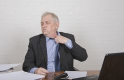 Stressed mature man at work loosening his tie. Sitting at a desk royalty free stock image