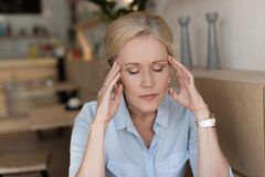 stressed mature woman with closed eyes having headache while stock images