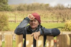 Stressed mature woman outdoors. Resting on fence royalty free stock photos
